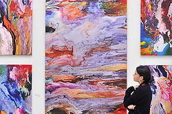 © Licensed to London News Pictures. 13/09/2017. London, UK. A staff member views works by Neil Kerman. Preview of the START Art Fair at the Saatchi Gallery in Chelsea.  The fair showcases the best emerging artists from developing markets across the globe and is open to the public 14 to 17 September. Photo credit : Stephen Chung/LNP