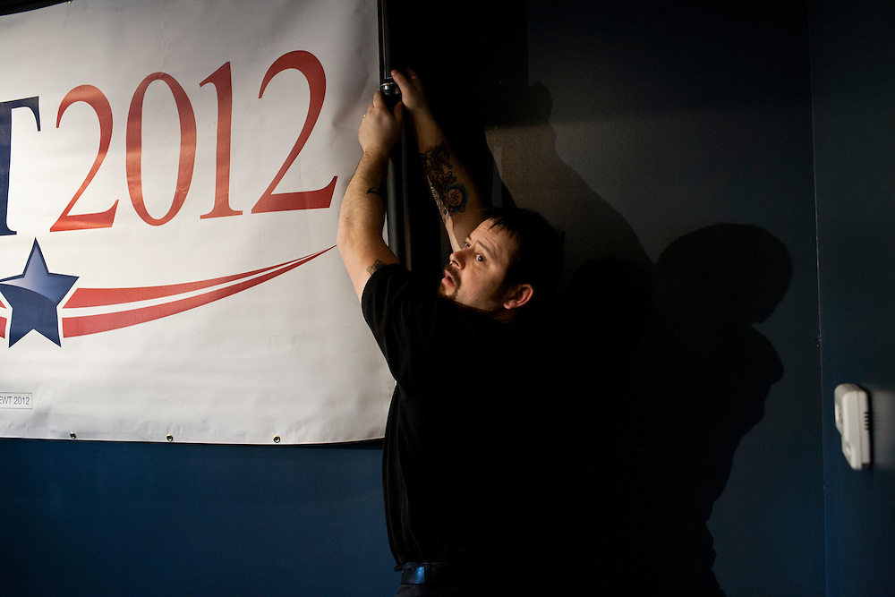 A campaign worker hangs a banner before a stop by Republican presidential candidate Newt Gingrich at Tish's Restaurant on Saturday, December 31, 2011 in Council Bluffs, IA.
