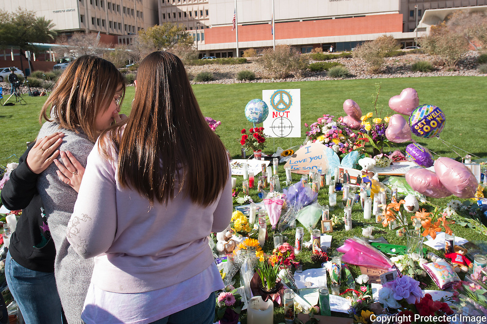 Three friends viw the memorial.  Located at the memorial in front of the University of Arizona Medical Center in Tucson, Arizona. The memorial was placed for the victims of the recent shooting in Tucson.
