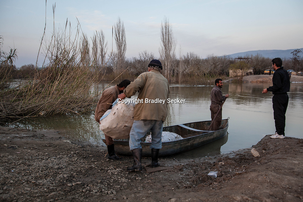 Syrian men loading a small boat with wood and plants, taking them to the villages on the Syrian side of the Orontes river which marks the border between the two countries. Feb 27th 2013, Hacipasa, Turkey