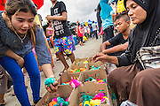 24 OCTOBER 2012 - PATTANI, PATTANI, THAILAND:  A Thai Buddhist woman buys colored baby chicks from a Muslim woman in a market in Pattani, Thailand. The chicks are colored by injecting their eggs with dyes. More than 5,000 people have been killed and over 9,000 hurt in more than 11,000 incidents, or about 3.5 a day, in Thailand's three southernmost provinces and four districts of Songkhla since the insurgent violence erupted in January 2004, according to Deep South Watch, an independent research organization that monitors violence in Thailand's deep south region that borders Malaysia. Muslim extremists are battling the Thai government and its symbols, like schools and Buddhist facilities.    PHOTO BY JACK KURTZ