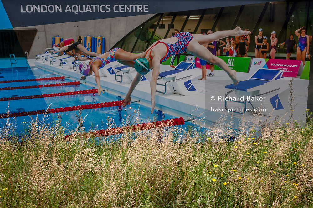 A construction hoarding featuring the Aquatics Centre used for water sports events during the 2012 Olympiad, on 16th August 2017, in the Queen Elizabeth Olympic Park, Stratford, East London, England.