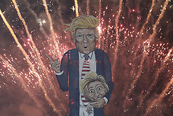 © Licensed to London News Pictures. 05/11/2016. Edenbridge, UK. An effigy of US Presidential candidate Donald Trump burns during the Edenbridge traditional fireworks display. The 36 ft tall figure is holding the head of his Democrat rival Hillary Clinton. Photo credit: Peter Macdiarmid/LNP