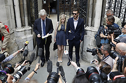 © Licensed to London News Pictures. 10/07/2017. Connie Yates and Chris Gard listen as a family friend (L) reads a statement to waiting reporters outside The High Court. The parents of terminally ill Charlie Gard are returning to court in light of claims of new evidence relating to potential treatment for his condition. An earlier lengthy legal battle ruled that Charlie could not be taken to the US for experimental treatment. London, UK. Photo credit: Peter Macdiarmid/LNP