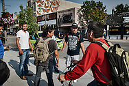 A group of men meet near a bank on payday. The migrant workers get time off each week to do their banking, shop and relax. It is the responsibility of the owners to provide a ride to and from town.