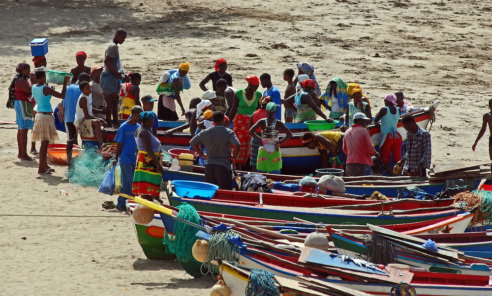 Brightly painted open wooden fishing boats hauled up on the beach and local girls gathered around to collect fish catch from fishermen, Tarrafal, North west Santiago, Cape Verde Islands (Cabo Verde).  Artisanal fisheries are still very important in the Cape Verdes. Many of these small boats are simply rowed by oars, some have small outboard motors.  Tarrafal, or Villa de Tarrafal,  is a small fishing port on the north western tip of Santiago.  It has a beautiful sandy beach.  Typical species caught include yellowfin tuna (Thunnus albacares), big-eye tuna (Thunnus obesus) and African hind (aka bluespotted seabass)(Cephalopholis taeniops).