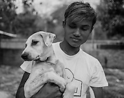 A caretaker at the Yangon Animal Shelter carries one of the rescued puppies.