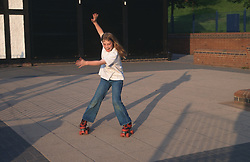 Young girl roller skating outdoors,
