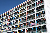 Clothes are aired in the sun and cover a residential building