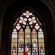 One of the colorful stained glass windows at the Cathedral of St. Michael and St. Gudula (in French, Co-Cathédrale collégiale des Ss-Michel et Gudule). A church was founded on this site in the 11th century but the current building dates to the 13th to 15th centuries. The Roman Catholic cathedral is the venue for many state functions such as coronations, royal weddings, and state funerals. It has two patron saints, St Michael and St Gudula, both of whom are also the patron saints of Brussels.
