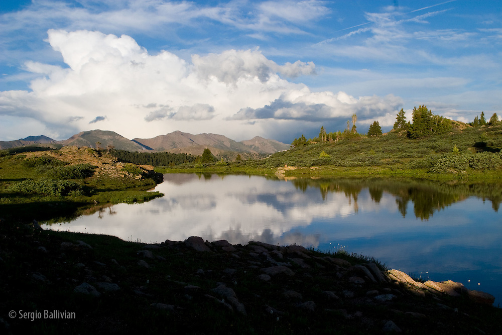 Blue sky reflected in a lake in an alpine valley of Taylor Pass near Ashcroft, Colorado