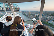 Tourists take photos out of the aerial view provided by the London Eye.