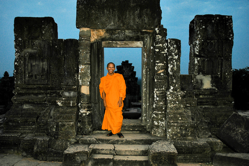 This sunset image of a monk in an ancient ruin of a door is from the hilltop temple in Angkor Wat. The Hill Temple of Phnom Bakheng is one of the most ancient of all the Angkor temples. It is popular as a sunset viewpoint with an average of 3000 people climbing it each day.<br />