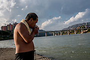 A man lights a cigarette after swimming in the Lancang (Mekong) river in Xishuangbanna, China.