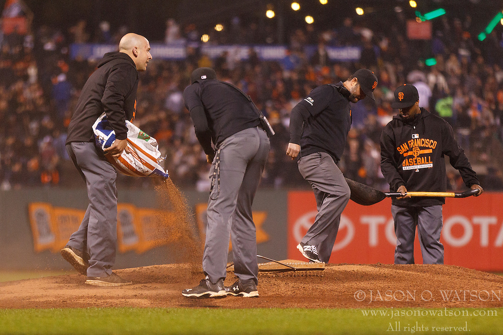 SAN FRANCISCO, CA - MAY 20:  Members of the San Francisco Giants grounds crew work on the pitchers mound in a rain storm during the eighth inning against the Los Angeles Dodgers at AT&T Park on May 20, 2015 in San Francisco, California. The San Francisco Giants defeated the Los Angeles Dodgers 4-0. (Photo by Jason O. Watson/Getty Images) *** Local Caption ***