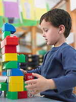 Boy playing with building blocks in classroom