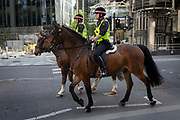Mounted City police officers patrol Leadenhall in the City of London - the capital's financial district, on 6th June 2018, in London, England.