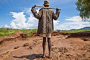 A maize farmer surveys damage to his crop following unseasonal heavy rains.