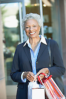 Smiling Woman standing outside holding Shopping Bags