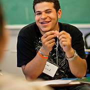 July 9, 2009 - Bronx, NY : Oscar Espinol smiles as he receives positive feedback on a response to a group discussion question. A group of 15 local high school students participated in the Kingsbridge Heights Community Center-sponsored summer literacy institute, an intensive 4-day college prep course.  The students, broken down into smaller groups and aided by student writing coaches and english teachers (Manhattan college students and alumns respectively) spent a total of 7-8 hours over three days discussing the college application process and preparing mock college application essays to be presented at a banquet on the fourth day.