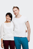 Portrait of young couple in casuals smiling over white background