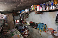 A boy is looking at a Bollywood movie in his home underneath a bridge by Bandra Station, Mumbai, India