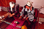 A handmade carpet of dyed wool takes shape on a horizontal loom  through the artistry of Bibit Ikhanova, left, and Zhanilya Bektasova in the village of Shieli.