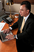 40 something executive working at his computer in a small office.