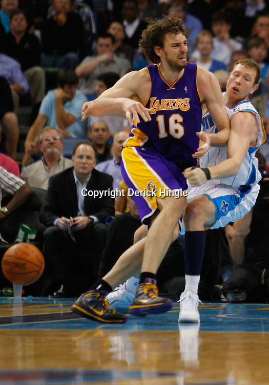 Mar 29, 2010; New Orleans, LA, USA; Los Angeles Lakers forward Pau Gasol (16) collides with New Orleans Hornets forward Darius Songaila (9) drawing a charging foul during the second half at the New Orleans Arena. Mandatory Credit: Derick E. Hingle-US PRESSWIRE