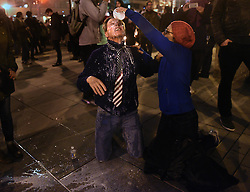January 20, 2017 - Washington, DC, U.S - Anti-Trump protester JULIA DA SILVA helps JEFF LEONARD, a Trump supporter during President Donald Trump's inauguration day in Washington, D.C., on Jan. 20, 2017. She pours milk after he got caught in the clash and took a direct hit in the face with pepper spray.  He repeated over and over ''I don't know why you're helping me. (Credit Image: © Carol Guzy via ZUMA Wire)