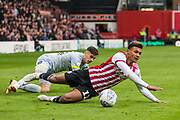Oliver Watkins (Brentford) falls during a tackle with Tom Lawrence (Derby County) during the EFL Sky Bet Championship match between Brentford and Derby County at Griffin Park, London, England on 6 April 2019.