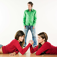 studio shot pictures on isolated background of two sisters twin women friends women fighting in arm wrestling for a man