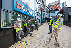 © Licensed to London News Pictures. 18/06/2020. Leeds UK. Builders use a tape measure to keep social distance outside a Greggs shop in Leeds city centre this morning as the store opens shops across the UK after the Covid-19 lockdown. Photo credit: Andrew McCaren/LNP