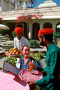 INDIA, RAJASTHAN Udaipur; a young woman in the garden of the famous Lake Palace Hotel on Lake Pichola being waited on by hotel staff