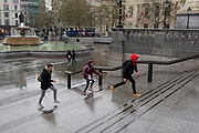 Youths leap up the steps to escape rain in Trafalgar Square, Westminster, on 9th April 2019, in London, England.