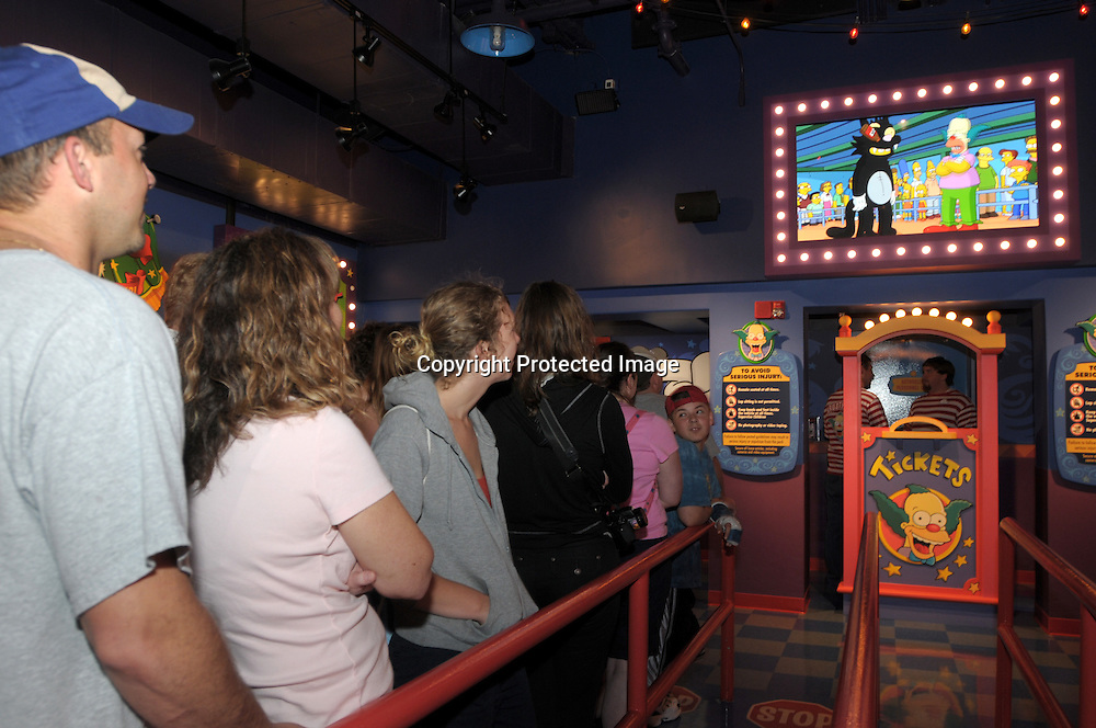 Tourists watch a pre-ride video while waiting in the queue of the newly-opened The Simpson's Ride at Universal Orlando in Orlando, Fla., Tuesday, April 29, 2008. (Photo by Phelan M. Ebenhack)