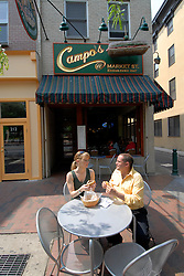 Couple eating at Campo's restaurant, outdoors, eating cheesesteaks, mod rel..Philadelphia, Pennsylvania, PA USA.  Photo copyright Lee Foster, 510-549-2202, lee@fostertravel.com, www.fostertravel.com. Photo 339-30498