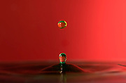 A water droplet falls on a coloured surface.