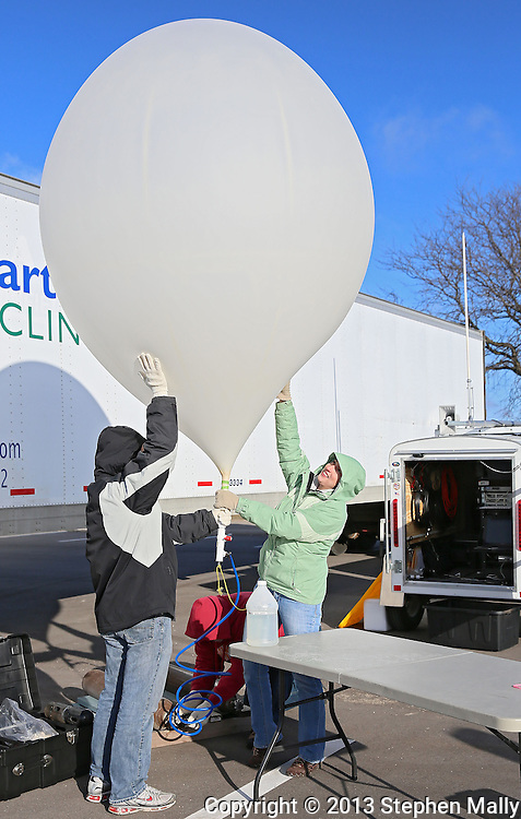 Fred Klauke (from left) of Iowa City, Steve Chmelar, and Sarah Dias, both of Ottumwa, work on filling the balloon as Iowa High Altitude Balloon Project, Cedar Valley Amateur Radio Club, Collins Amateur Radio Club, and Rockwell Collins, Inc. launch a high altitude balloon to start Engineers Week at Rockwell Collin in Cedar Rapids on Saturday, February 16 2013. Klauke, Chmelar, and Dias all help with Iowa High Altitude Balloon Project.