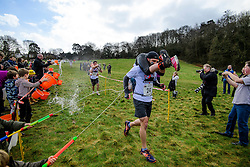 © Licensed to London News Pictures. 05/03/2017. Dorking, UK. Water being thrown over competitors as they take part in the 2017 Wife Carrying Race in Dorking, Surrey.  The race, which is run over a course of 380m, with both men and women carry a 'wife' over obstacles,  is believed to have originated in the UK over twelve centuries ago when Viking raiders rampaged into the northeast coast of  England carrying off any unwilling local women.  Photo credit: Ben Cawthra/LNP