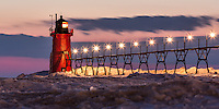The South Haven lighthouse stands out boldly against the color striped sky