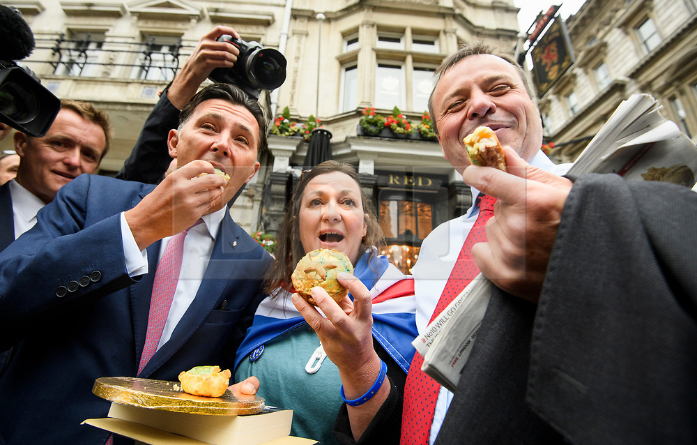 © Licensed to London News Pictures. 12/06/2018. London, UK.  A remain supporter presents pork pies to Leave.EU founder ARRON BANKS and Leave.EU campaigner ANDY WIGMORE as they arrive at Portcullis House in London where they are due to give evidence to a Commons Digital, Culture, Media and Sport Committee about fake news. The pair have been accused of collusion with Russian officials around the time of the Brexit referendum. Photo credit: Ben Cawthra/LNP