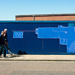 London, UK - 23 July 2012: Two men walk past a graffiti wall in Hackney Wick, close to the London 2012 Olympic Park. The area, once a major  manufacturing center in the UK, is now a mix of old warehouses converted into artist's studio and industrial yards attracting now both tourists and Olympic staff members