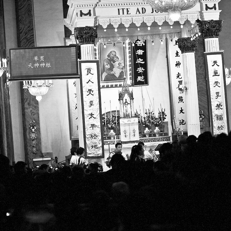 Midnight mass in Beijing in the official catholic church of Wangfujing . On the left side, the text of prayers is displayed on an electronic panel for those who come for the fisrt time. A large part of the public is composed by young chinese who rediscover this religion.