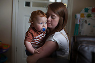 Baby Oliver-James Giles is comforted by his mother Victoria Cunningham  in the house the family rents in Bradford, Great Britain Monday, May 26, 2014. Through Save the Children's EAT, SLEEP, LEARN AND PLAY programme the family was awarded a fridge freezer and a toy and book pack. A record five million children in the UK could be trapped in poverty by 2020, according to new research by Save the Children. The report reveals that children have paid the highest price in the recession, with families having been hit by years of flat wages, cut to benefits and the rising cost of living. (Elizabeth Dalziel for Save the Children )