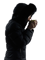 one woman in winter coat drinking hot drink silhouette on white background