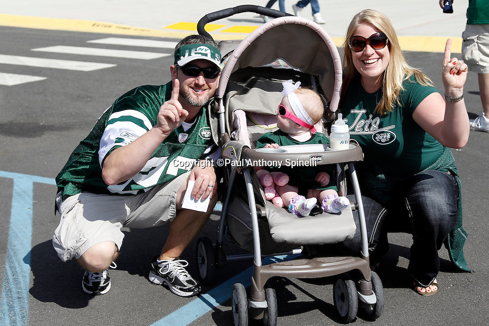 New York Jets fans pose for a photo and give the number one sign with their baby dressed up in Jets gear during the NFL week 2 football game against the Jacksonville Jaguars on Sunday, September 18, 2011 in East Rutherford, New Jersey. The Jets won the game 32-3. ©Paul Anthony Spinelli
