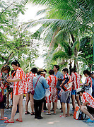 A group of Korean tourists in matching shirts collect souvenirs after a boat trip.