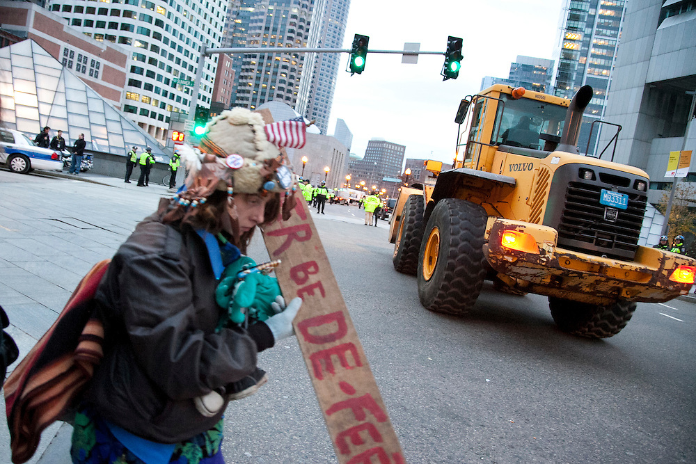 A bulldozer heads to Dewey Square to take away debris as an  Occupy Boston member cross a street in Boston, Massachusetts, December 10, 2011.