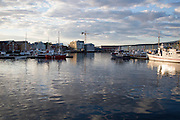 Late summer evening near midnight boats in harbour, city centre of Tromso, Norway